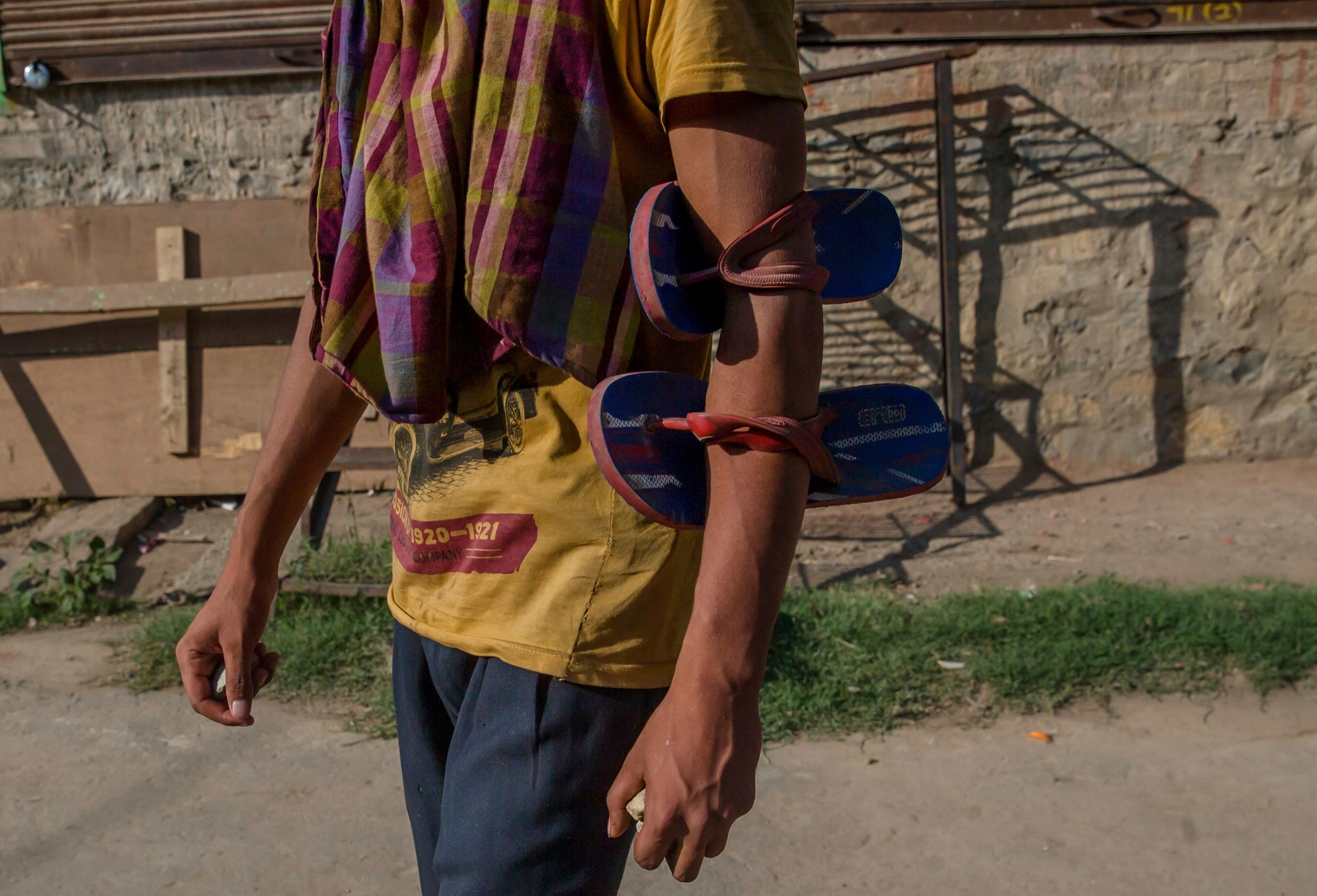 A villager has his slippers tied to his arm as he holds stones before throwing them at Indian policemen to protest during the funeral procession of a civilian Tanveer Ahmed Wani, in Beerwah about 25 miles (40 km.) west of Srinagar on July 21, 2017. The Indian army fired at worshippers outside a mosque in disputed Kashmir on Friday, killing one man and injuring another, after some threw rocks, police and residents said.