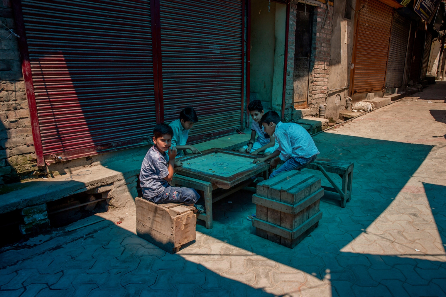 Boys play caromboard on a road outside during a strike in Srinagar on June 9, 2017. Parts of Indian-controlled Kashmir remained under curfew Friday, while general strikes were being staged in other areas after Kashmiri separatists called for strike to protest the Tuesday killing of a civilian by government forces during a search operation to flush out Kashmiri rebels in the southern town of Indian controlled Kashmir.