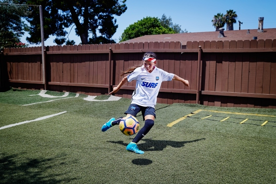 "Melanie Barcenas, 9, practicing in her San Diego backyard, hopes to follow in the footsteps of the superstar Neymar. ""He plays just like me,"" she says. Melanie plays multiple soccer games most weekends. To save money, her family stays in a hotel only if a game is more than a four-hour drive from home. Here Melanie is photographed at home where her father Carlos made a practice field for her in their backyard, on Aug. 3, 2017."