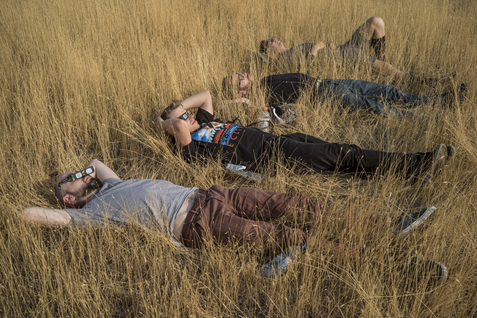 Four men relax before the time the moon will have full coverage over the sun in a field overlooking this small town which is in the path of totality in Madras, Ore., on Aug. 21, 2017.