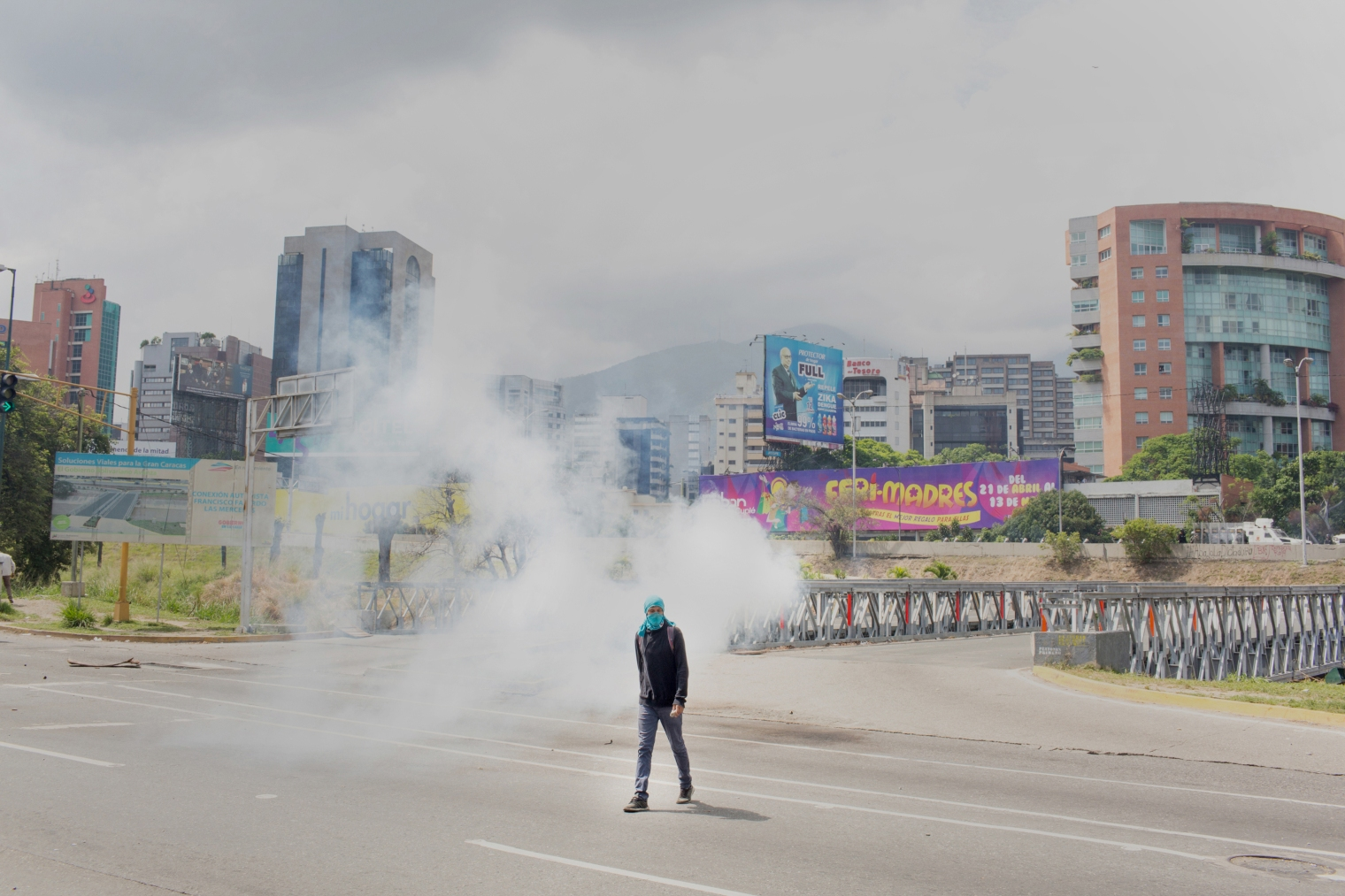 A masked protester walks during a clash with authorities after a silent march honoring the martyrs in Caracas on April 22, 2017.