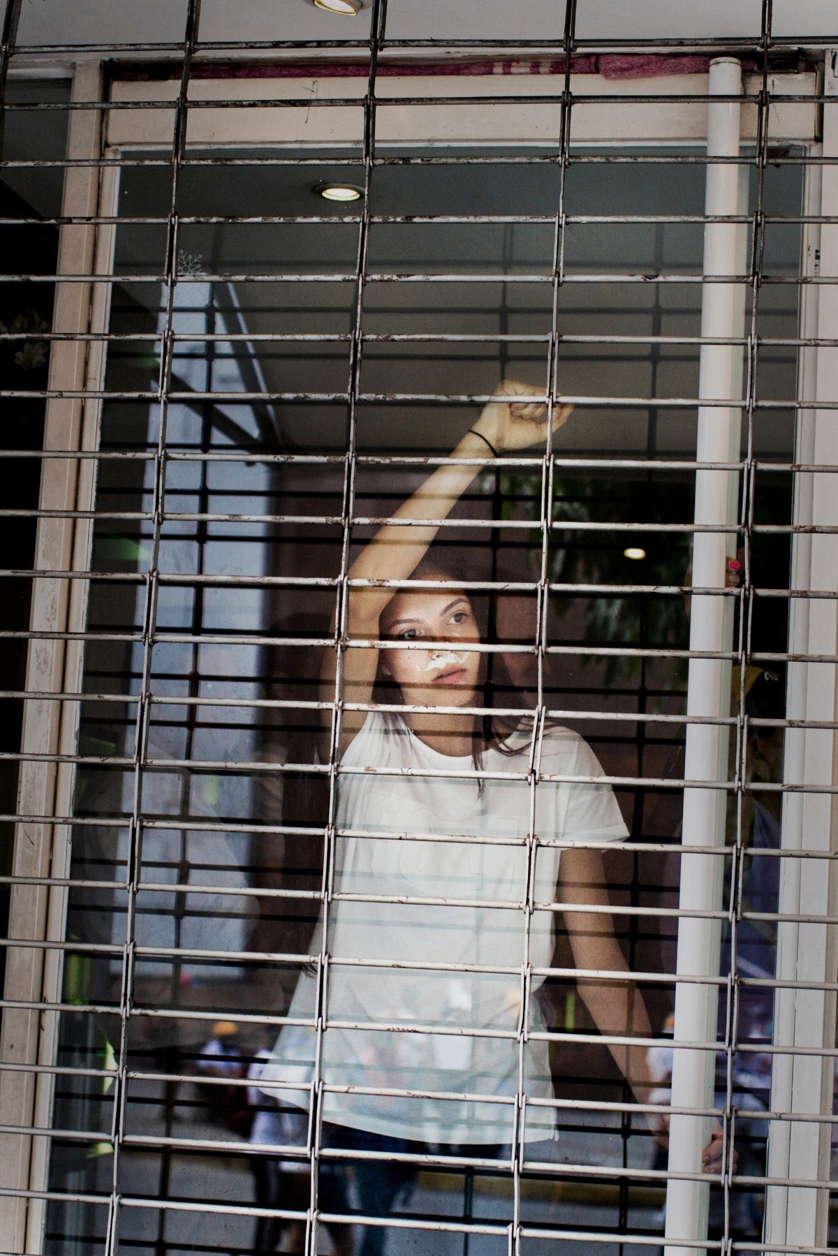 A woman watches from the window of a shuttered store as protesters run from the National Guard in the commercial area of Las Mercedes in Caracas on May 1, 2017.