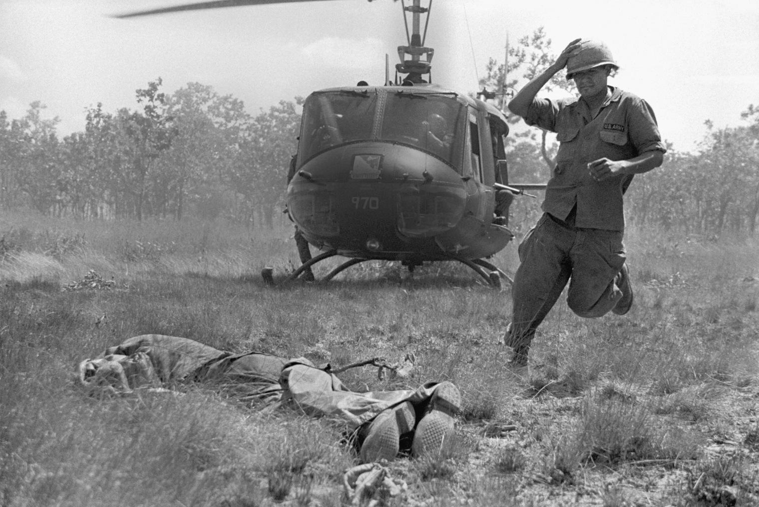Soldier Picking Up Dead Body In Vietnam
