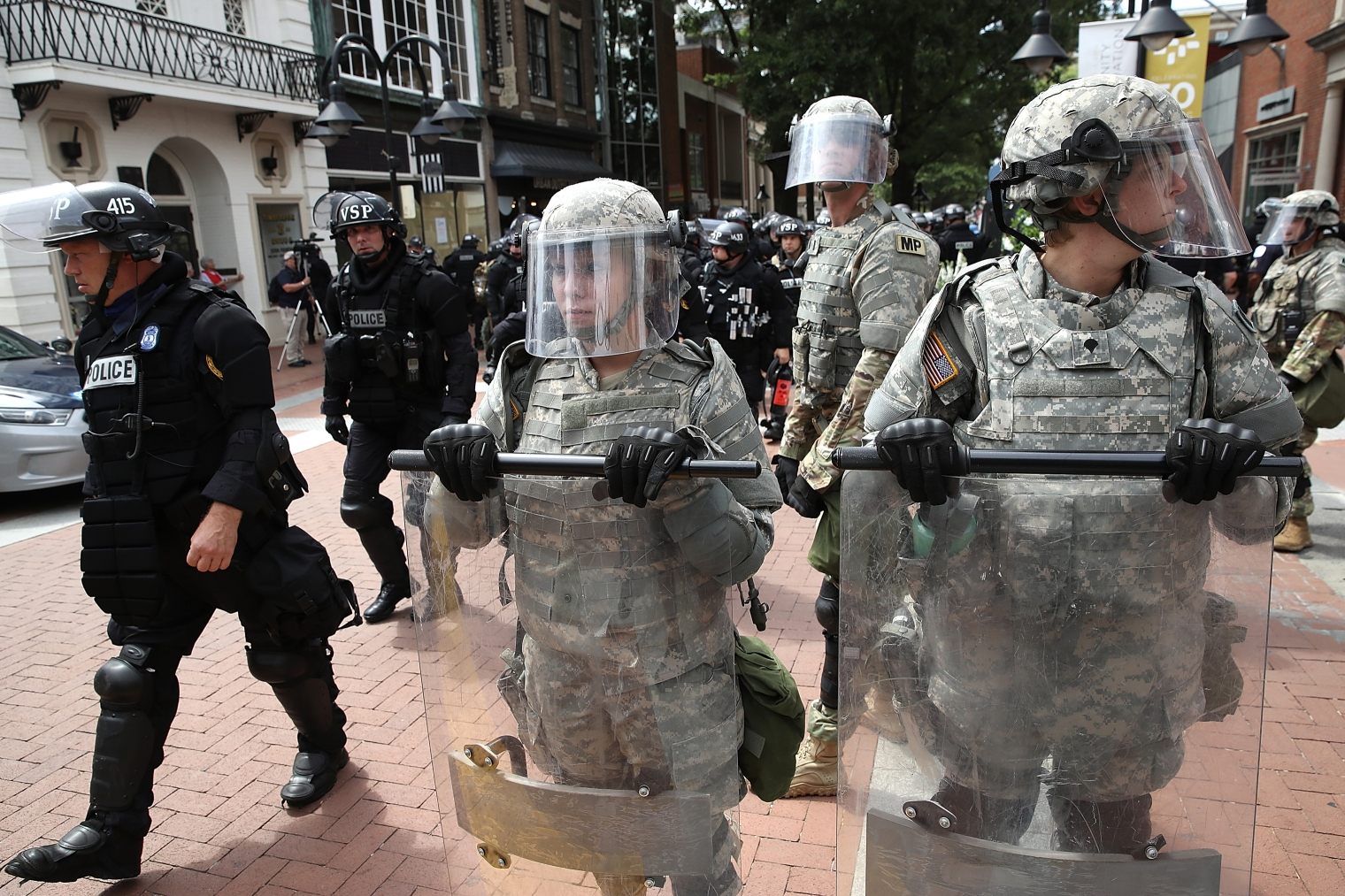 Police and members of the National Guard patrol near the location where a car plowed into a crowd of people marching through a downtown shopping district in Charlottesville, Va., on Aug. 12, 2017.