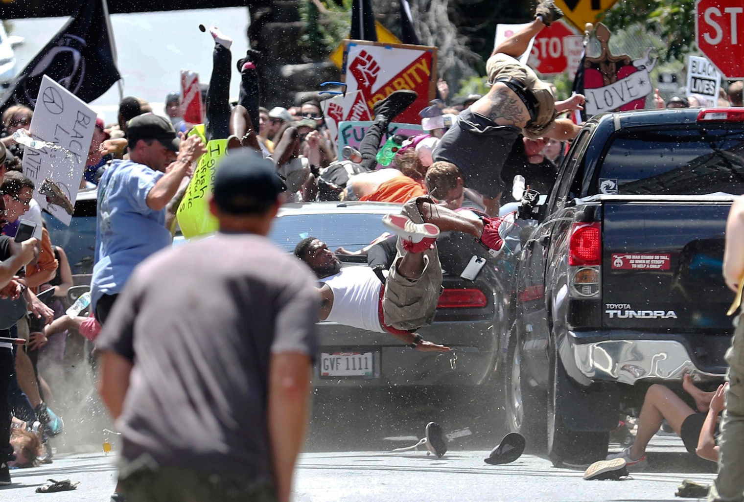 People fly into the air as a vehicle drives into a group of protesters demonstrating against a white nationalist rally