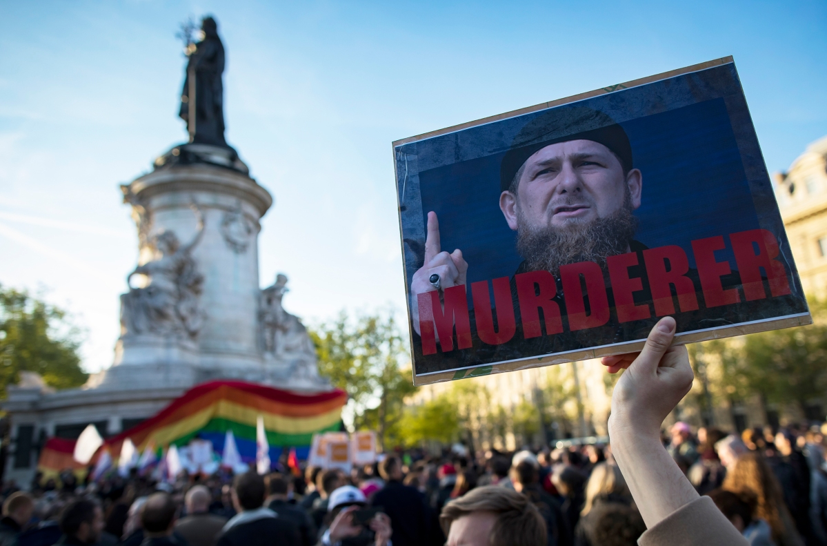 A demonstrator holders a sign depicting Chechen leader Ramzan Kadyrov with the label