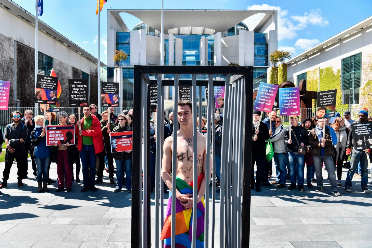 An activist stands naked, wrapped in a rainbow flag, in a mock cage in front of the Chancellery in Berlin on April 30, 2017, during a demonstration calling on Russian President to put an end to the persecution of gay men in Chechnya
