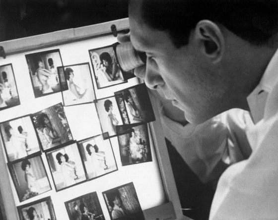 Playboy Publisher Hugh Hefner Observing Photographs