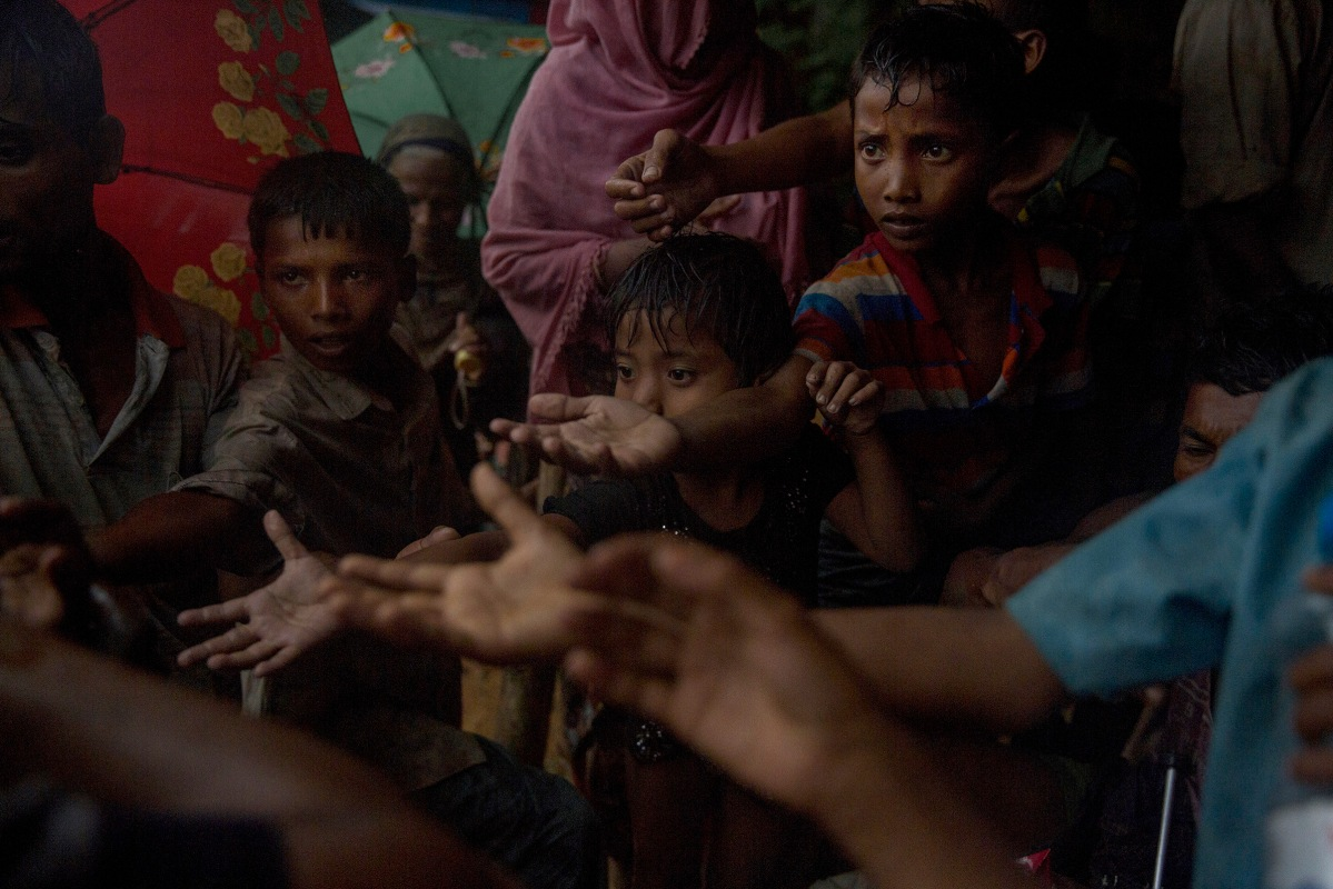 A local is distributing biscuits to Rohingya refugees children in Kutupalong station.The United Nations says 87,000 mostly Rohingya refugees have poured over the border into Bangladesh since the latest round of fighting broke out 10 days ago in Myanmar's neighbouring Rakhine state.The Rohingya are a mainly Muslim stateless ethnic minority who according to rights groups have faced decades of persecution in mainly Buddhist Myanmar. Bangladesh was already home to around 400,000 Rohingya before the current crisis. Figures on Sept 5th, 2017.