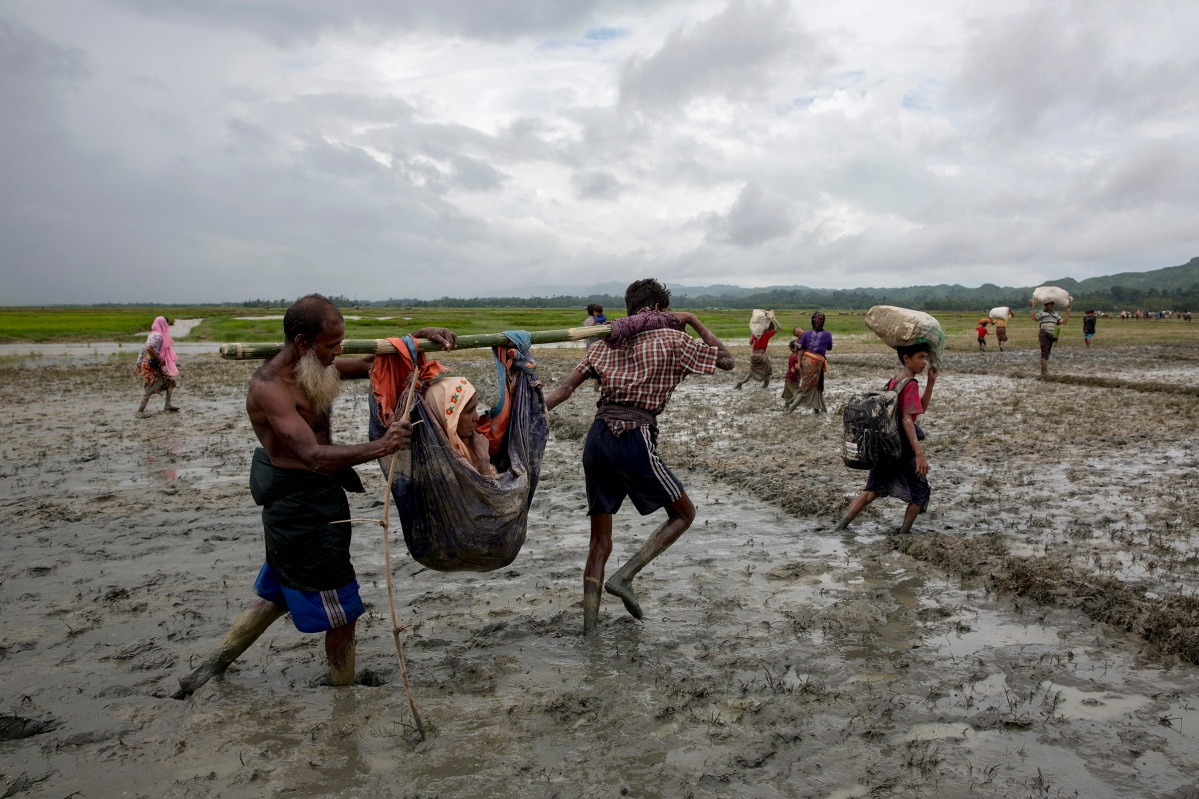 Rohingya refugees carry an elderly woman after crossing the border into Bangladesh, August 31, 2017.