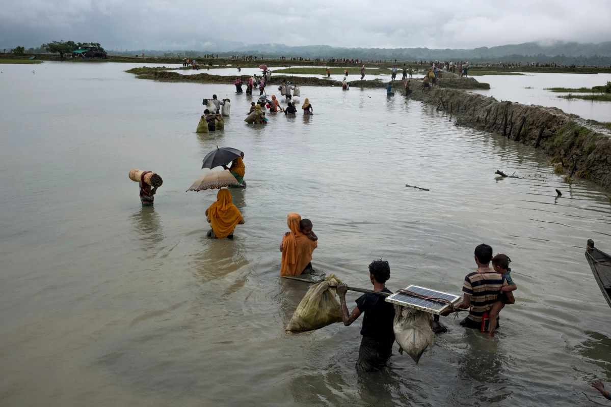 Members of Myanmar's Rohingya ethnic minority walk in flooded land after crossing the border into Bangladesh, September 1, 2017.