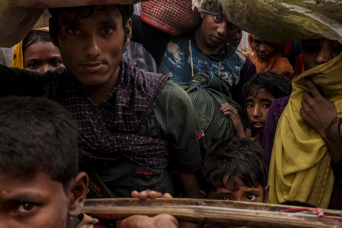 Rohingya refugees wait in line to be allowed by Bangladesh border guards to enter Unchiprang village after crossing the border into Bangladesh, September 1, 2017.