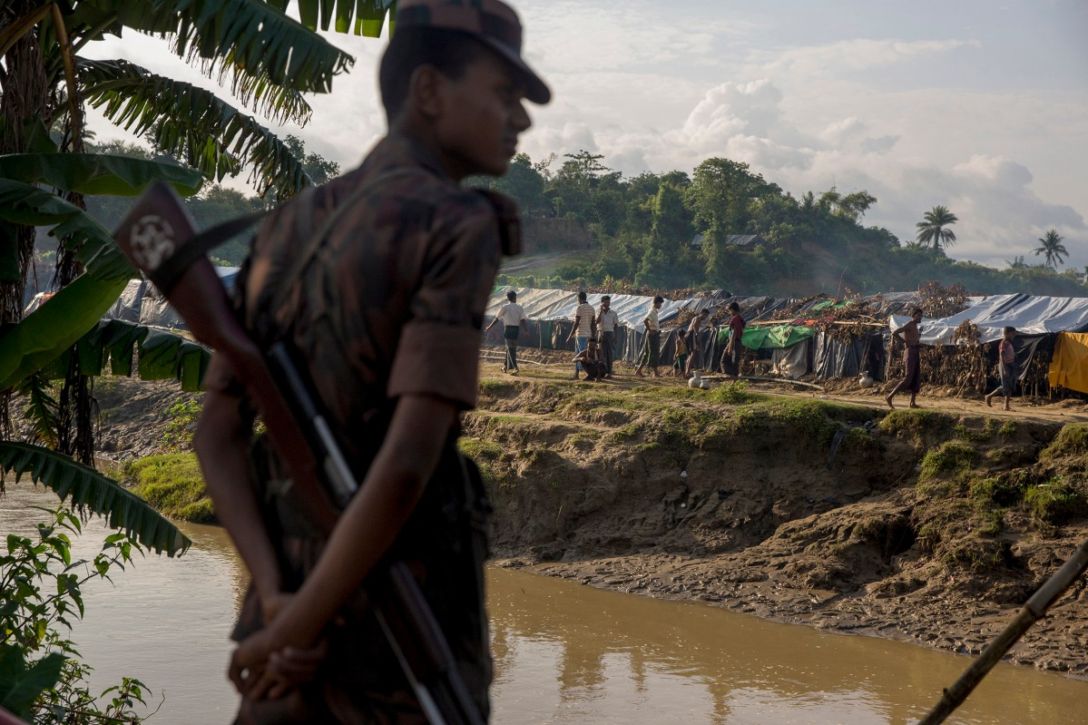 A border guard from Bangladesh maintains a group of several thousands Rohingya refugees in a no man's land inside Bangladesh territory, close to the border with Myanmar. They just allow children to cross the river to collect food and water. September 1, 2017.