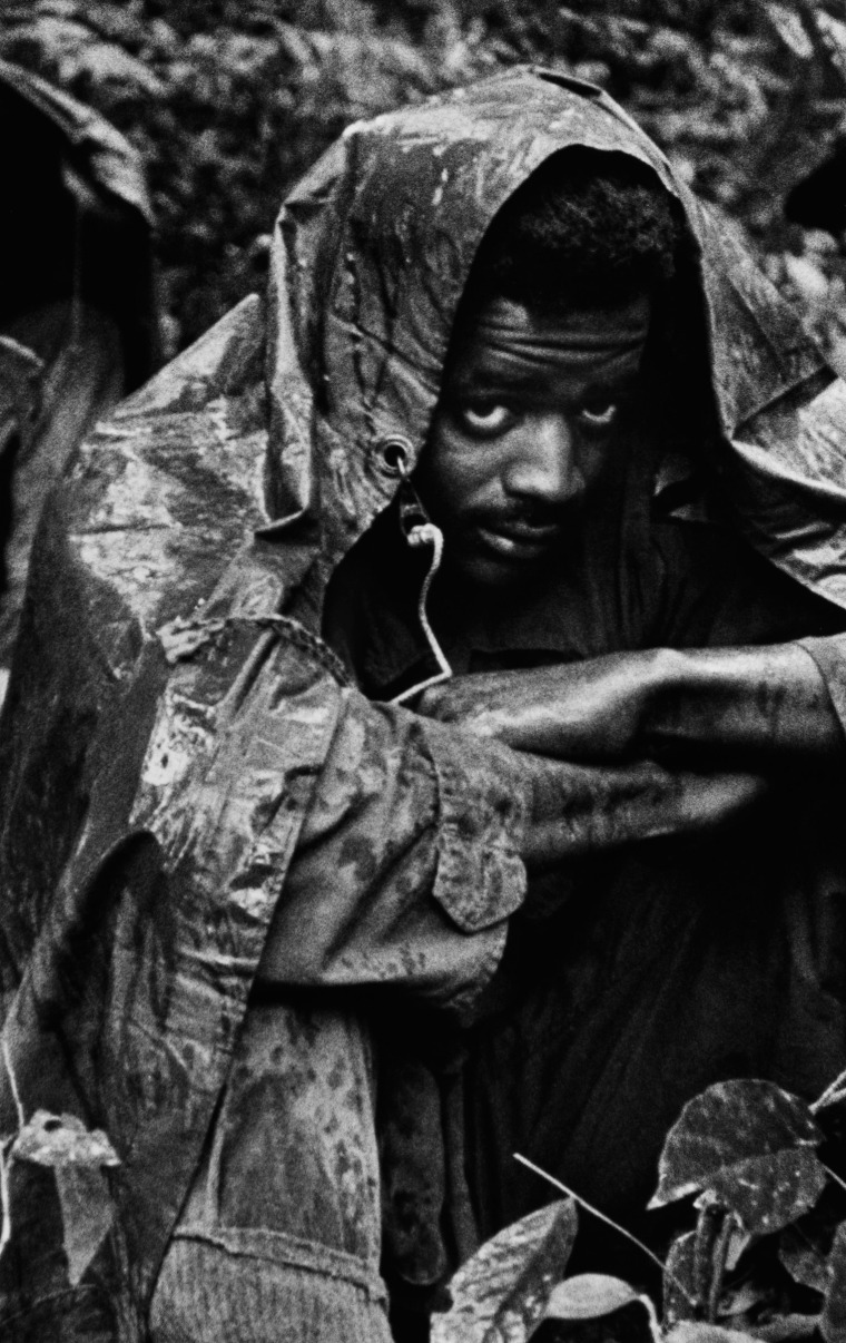 NEAR DA NANG — 1972: A GI on patrol in the jungles near Da Nang, South Vietnam, huddles under a poncho to escape the monsoon rains, 1972. (Photo by David Hume Kennerly)