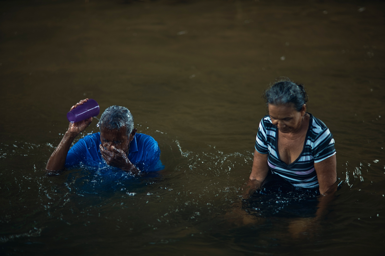 Luis Pinto, 73, and his neighbor Rosa Fernandez, 62, bathe in the river in Juncos, Puerto Rico, on Sept. 29, 2017.