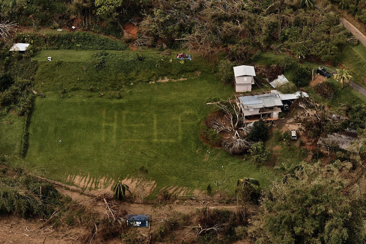 "The desperate message ""HELP"" is seen on the lawn of a home near Utuado, Puerto Rico, in early October. Photographer @andreskudacki, who was covering the aftermath of Hurricane Maria for TIME, came across this scene during a helicopter flyover in the central mountainous region, where rescuers had previously searched for those in need. Police who originally saw the sign landed to find people without food or water, isolated as a nearby river swelled."