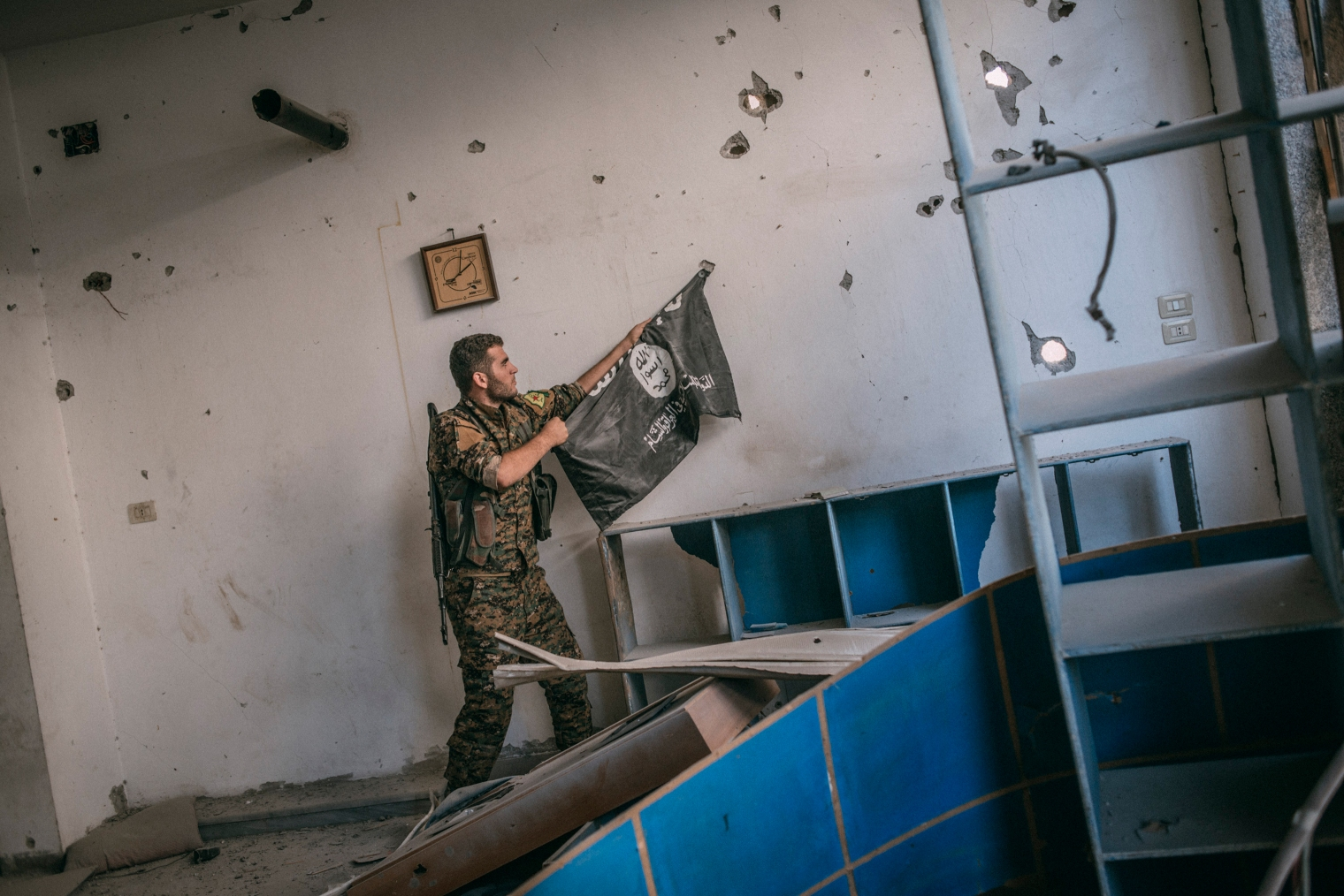 A member of the Syrian Democratic Forces removes an Islamic State flag from a wall in Raqqa on Oct. 18, 2017.