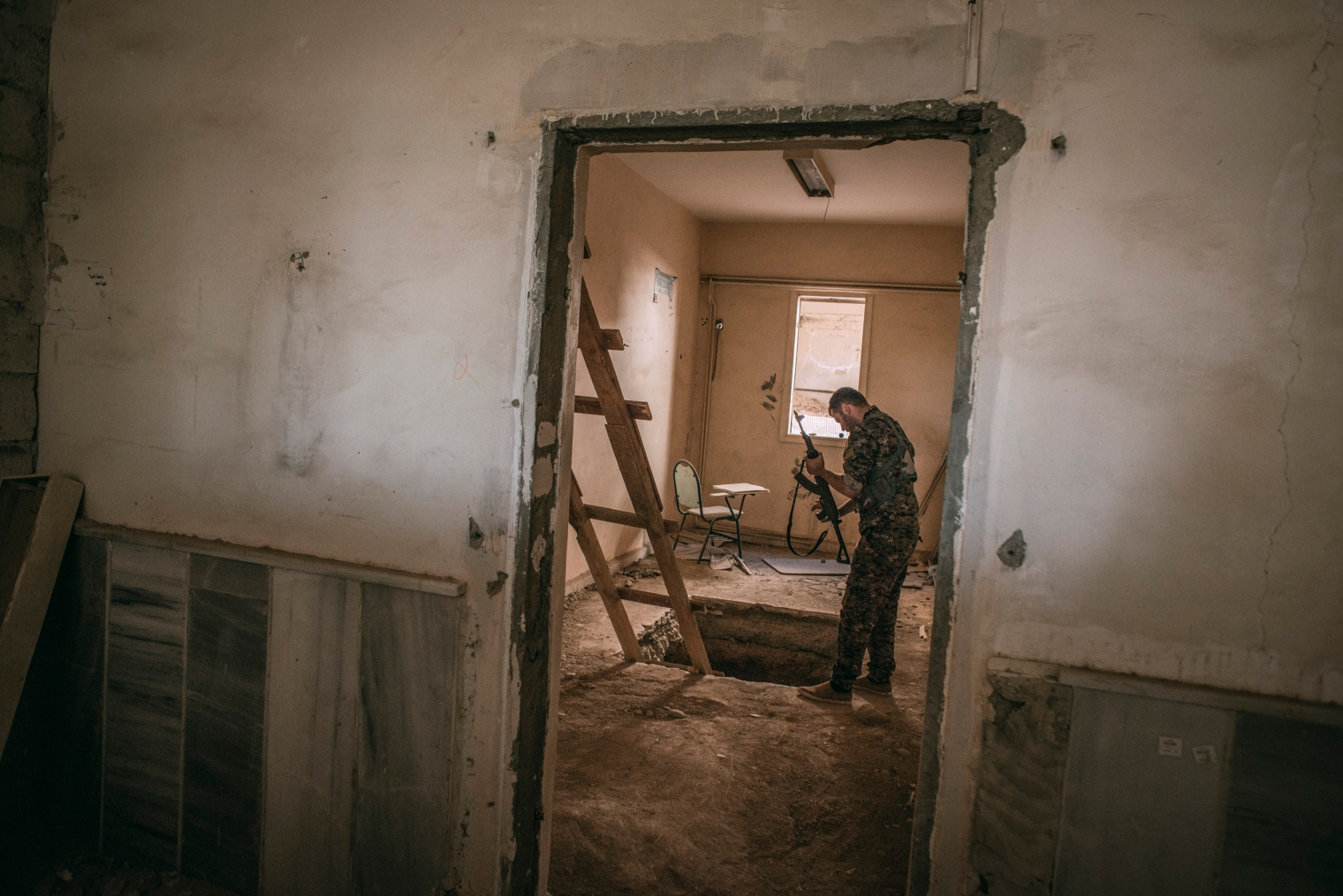A member of the Syrian Democratic Forces inspects an Islamic State tunnel inside a college in Raqqa on Oct. 18, 2017.