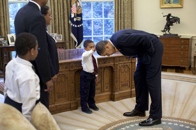 President Barack Obama bends over so Jacob Philadelphia can pat his head on May 8, 2009.