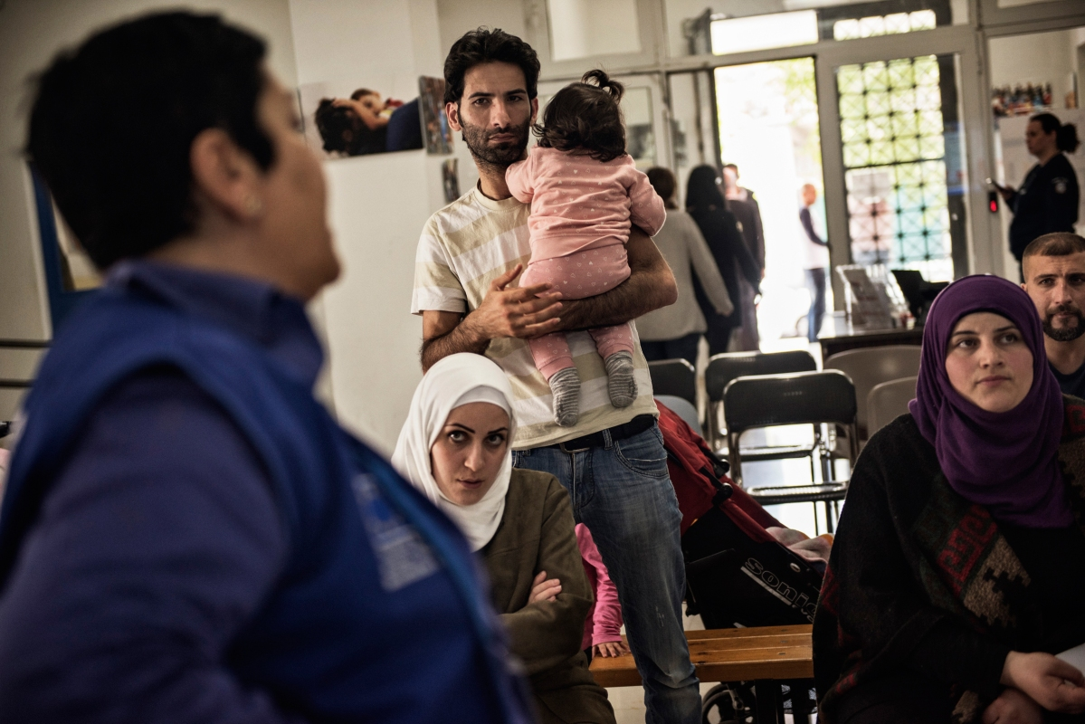 Syrian refugees TaIma Abzali and her husband Muhanned Abzali, and their six month old daughter, Heln, and son Wael, attend a final orientation meeting at the International Organisation for Migration the day before leaving for relocation in Estonia, April 19, 2017. The family then returns home and packs their belongings, trying to stuff their lives into one 20kg suitcase each, in Athens, Greece. (Credit: Lynsey Addario for Time Magazine)