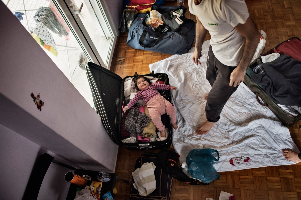 Syrian refugee Muhanned Abzali, jokes with his 6 month old daughter, Heln, by packing her in a suitcase, the night before leaving for relocation in Estonia, April 19, 2017. Muhanned's wife, Taima, was overcome with emotion, a nostalgia for Syria, and missing her family, as she packed. (Credit: Lynsey Addario for Time Magazine)