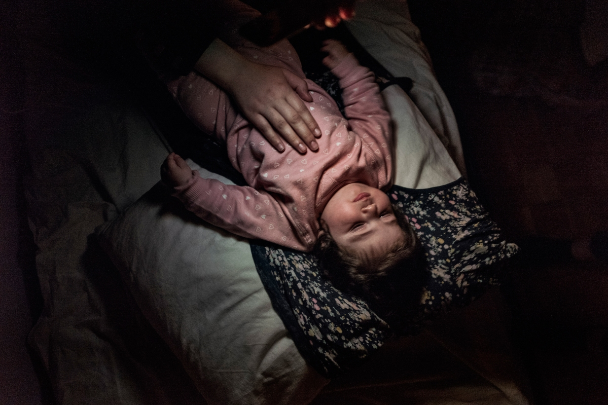 """<span class=""""credit"""">Syrian refugee Heln is rocked to sleep with the light of an iphone by a Syrian refugee friend of Taima, the night before the family travels from Athens to Estonia for relocation April 19, 2017. (Credit: Lynsey Addario for Time Magazine)</span><span class=""""caption"""">Syrian refugee Heln is rocked to sleep with the light of an iphone by a Syrian refugee friend of Taima, the night before the family travels from Athens to Estonia for relocation April 19, 2017. (Credit: Lynsey Addario for Time Magazine)</span>"""
