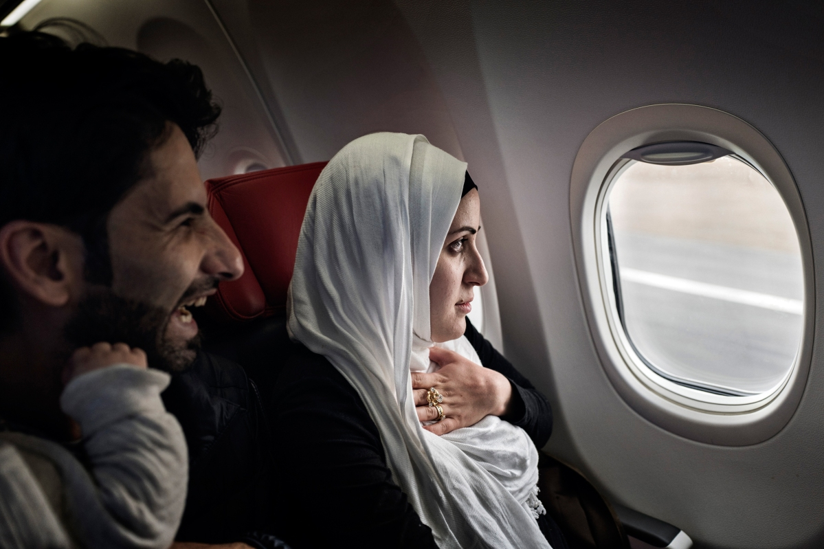 """<span class=""""credit"""">Syrian refugees TaIma Abzali and her husband Muhanned Abzali, look out the window with a mix of fear and excitement as they see Estonia from the air for the first time, April 20, 2017. After over one year of traveling from war-town Syria, making their way from Turkey to Greece, waiting in greece for asylum, the family is finally relocating to Estonia. (Credit: Lynsey Addario for Time Magazine)</span><span class=""""caption"""">Syrian refugees TaIma Abzali and her husband Muhanned Abzali, look out the window with a mix of fear and excitement as they see Estonia from the air for the first time, April 20, 2017. After over one year of traveling from war-town Syria, making their way from Turkey to Greece, waiting in greece for asylum, the family is finally relocating to Estonia. (Credit: Lynsey Addario for Time Magazine)</span>"""