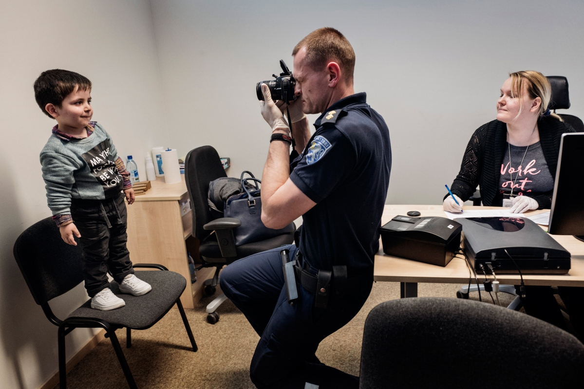 """<span class=""""credit"""">Syrian refugee Wael Abzali is fingerprinted and photographed by Estonian border officials in the airport in Talinn upon arrival in Estonia, April 20, 2017. After over one year of traveling from war-town Syria, making their way from Turkey to Greece, waiting in greece for asylum, the family is finally relocating to Estonia. (Credit: Lynsey Addario for Time Magazine)</span><span class=""""caption"""">Syrian refugee Wael Abzali is fingerprinted and photographed by Estonian border officials in the airport in Talinn upon arrival in Estonia, April 20, 2017. After over one year of traveling from war-town Syria, making their way from Turkey to Greece, waiting in greece for asylum, the family is finally relocating to Estonia. (Credit: Lynsey Addario for Time Magazine)</span>"""
