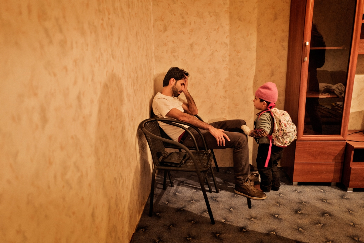 """<span class=""""credit"""">Syrian refugee Muhanned Abzali sits, exhausted, as his son, Wael, stands beside him moments after arriving for the first time into the family's new apartment after a long, grueling day of travel and unheaval once again from Athens to their new home in Polva, Estonia, April 20, 2017. The family, along with Muhanned's brother's family of Mufeed and Iman Ateek and their two children, were relocated to a small village of 6000 people in the middle of the forest, called Polva; they feared it would be impossible to integrate and make a life in such a remote place. After over one year of traveling from war-town Syria, making their way from Turkey to Greece, waiting in greece for asylum, the family is finally relocating to Estonia. (Credit: Lynsey Addario for Time Magazine)</span><span class=""""caption"""">Syrian refugee Muhanned Abzali sits, exhausted, as his son, Wael, stands beside him moments after arriving for the first time into the family's new apartment after a long, grueling day of travel and unheaval once again from Athens to their new home in Polva, Estonia, April 20, 2017. The family, along with Muhanned's brother's family of Mufeed and Iman Ateek and their two children, were relocated to a small village of 6000 people in the middle of the forest, called Polva; they feared it would be impossible to integrate and make a life in such a remote place. After over one year of traveling from war-town Syria, making their way from Turkey to Greece, waiting in greece for asylum, the family is finally relocating to Estonia. (Credit: Lynsey Addario for Time Magazine)</span>"""