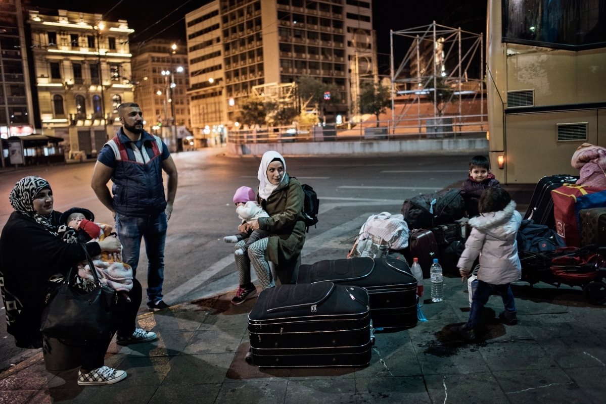 Syrian refugees TaIma Abzali and her husband Muhanned Abzali, and their six month old daughter, Heln, and son Wael, wait in Athen's Ommonia square for transfer to the airport alongside Muhanned's brother, Mufeed, his wife, Iman, and their two children, from Athens to Estonia for relocation April 20, 2017. The two families with join a handful of other Syrian families in their relocation to Estonia. (Credit: Lynsey Addario for Time Magazine)