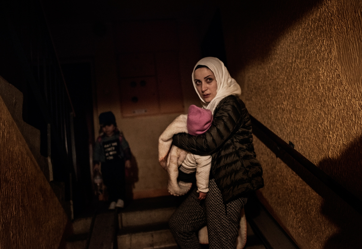 """<span class=""""credit"""">Syrian refugee Taima Abzali weeps as she holds baby Heln and enters her new apartment building after a long, grueling day of travel and unheaval once again from Athens to their new home in Polva, Estonia, April 20, 2017. She says """"It's better Heln won't remember anything."""" CHECK THIS QUOTE WITH ARYN The family, along with Muhanned's brother's family of Mufeed and Iman Ateek and their two children, were relocated to a small village of 6000 people in the middle of the forest, called Polva; they feared it would be impossible to integrate and make a life in such a remote place. After over one year of traveling from war-town Syria, making their way from Turkey to Greece, waiting in greece for asylum, the family is finally relocating to Estonia. (Credit: Lynsey Addario for Time Magazine)</span><span class=""""caption"""">Syrian refugee Taima Abzali weeps as she holds baby Heln and enters her new apartment building after a long, grueling day of travel and unheaval once again from Athens to their new home in Polva, Estonia, April 20, 2017. She says """"It's better Heln won't remember anything."""" CHECK THIS QUOTE WITH ARYN The family, along with Muhanned's brother's family of Mufeed and Iman Ateek and their two children, were relocated to a small village of 6000 people in the middle of the forest, called Polva; they feared it would be impossible to integrate and make a life in such a remote place. After over one year of traveling from war-town Syria, making their way from Turkey to Greece, waiting in greece for asylum, the family is finally relocating to Estonia. (Credit: Lynsey Addario for Time Magazine)</span>"""