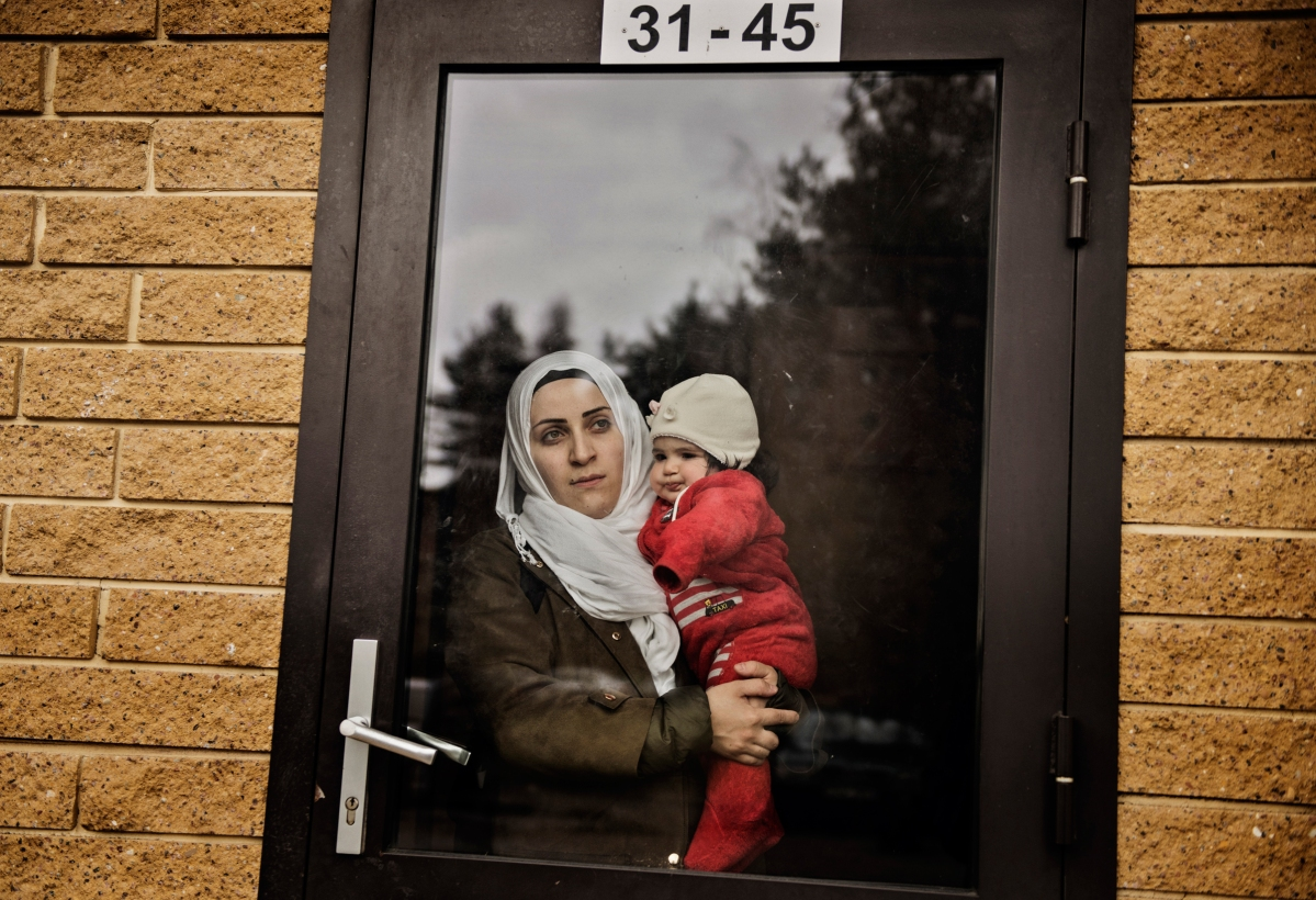 """<span class=""""credit"""">Syrian refugee Taima Abzali stares out the window of her apartment building front door as she holds baby Heln the morning after a long, grueling day of travel and upheaval once again from Athens to their new home in Polva, Estonia, April 20, 2017. She says """"It's better Heln won't remember anything."""" CHECK THIS QUOTE WITH ARYN The family, along with Muhanned's brother's family of Mufeed and Iman Ateek and their two children, were relocated to a small village of 6000 people in the middle of the forest, called Polva; they feared it would be impossible to integrate and make a life in such a remote place. After over one year of traveling from war-town Syria, making their way from Turkey to Greece, waiting in greece for asylum, the family is finally relocating to Estonia. (Credit: Lynsey Addario for Time Magazine)</span><span class=""""caption"""">Syrian refugee Taima Abzali stares out the window of her apartment building front door as she holds baby Heln the morning after a long, grueling day of travel and upheaval once again from Athens to their new home in Polva, Estonia, April 20, 2017. She says """"It's better Heln won't remember anything."""" CHECK THIS QUOTE WITH ARYN The family, along with Muhanned's brother's family of Mufeed and Iman Ateek and their two children, were relocated to a small village of 6000 people in the middle of the forest, called Polva; they feared it would be impossible to integrate and make a life in such a remote place. After over one year of traveling from war-town Syria, making their way from Turkey to Greece, waiting in greece for asylum, the family is finally relocating to Estonia. (Credit: Lynsey Addario for Time Magazine)</span>"""