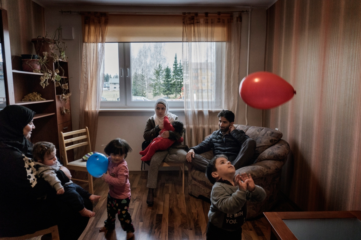 """<span class=""""credit"""">Syrian refugees Muhanned and TaIma Abzali and their two children sit with Muhanned's brother's family of Mufeed and Iman Ateek and their two children in Mufeed and Iman's new apartment about one mile from Muhanned and Taima's in Polva, Estonia, April 20, 2017. The two families were relocated to a small village of 6000 people in the middle of the forest, called Polva; they feared it would be impossible to integrate and make a life in such a remote place. After over one year of traveling from war-town Syria, making their way from Turkey to Greece, waiting in greece for asylum, the family is finally relocating to Estonia. (Credit: Lynsey Addario for Time Magazine)</span><span class=""""caption"""">Syrian refugees Muhanned and TaIma Abzali and their two children sit with Muhanned's brother's family of Mufeed and Iman Ateek and their two children in Mufeed and Iman's new apartment about one mile from Muhanned and Taima's in Polva, Estonia, April 20, 2017. The two families were relocated to a small village of 6000 people in the middle of the forest, called Polva; they feared it would be impossible to integrate and make a life in such a remote place. After over one year of traveling from war-town Syria, making their way from Turkey to Greece, waiting in greece for asylum, the family is finally relocating to Estonia. (Credit: Lynsey Addario for Time Magazine)</span>"""