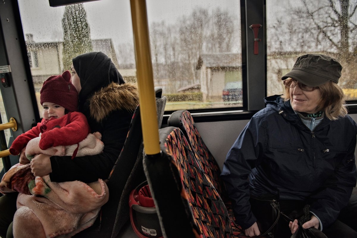 """<span class=""""credit"""">An Estonian woman looks over at Syrian refugees Taima Abzali and six month old daughter, Heln, on the bus from Polva to Tartu, where the family will have their orientation with IOM on their second full day in Estonia, April 21, 2017. The family is struggling to cope with the weather and the stark difference in culture in Estonia. (Credit: Lynsey Addario for Time Magazine)</span><span class=""""caption"""">An Estonian woman looks over at Syrian refugees Taima Abzali and six month old daughter, Heln, on the bus from Polva to Tartu, where the family will have their orientation with IOM on their second full day in Estonia, April 21, 2017. The family is struggling to cope with the weather and the stark difference in culture in Estonia. (Credit: Lynsey Addario for Time Magazine)</span>"""