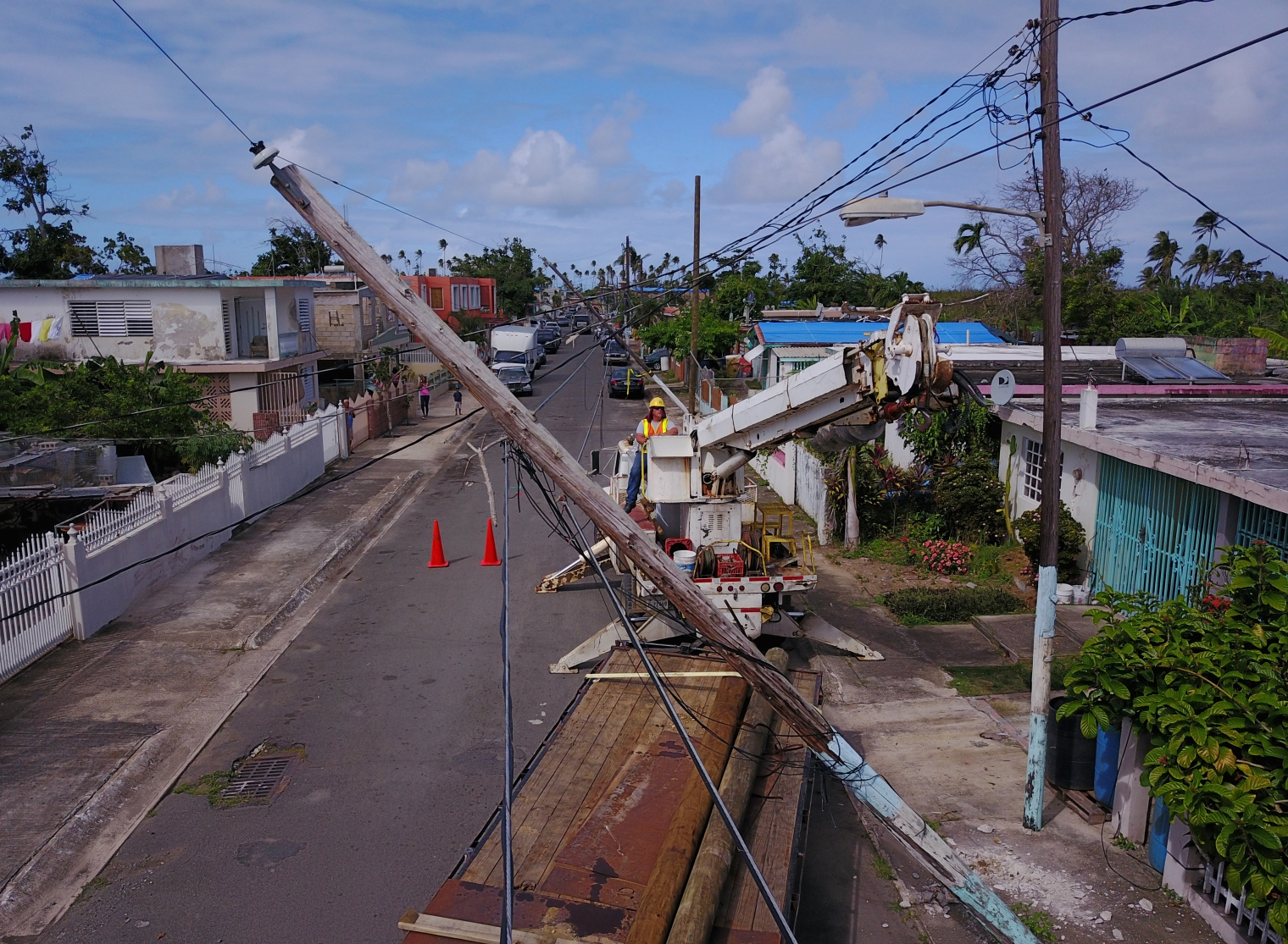 Utility workers replace a power pole in Loiza