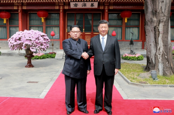 Kim Jong Un and Xi Jinping shake hands at the Diaoyutai State Guesthouse
