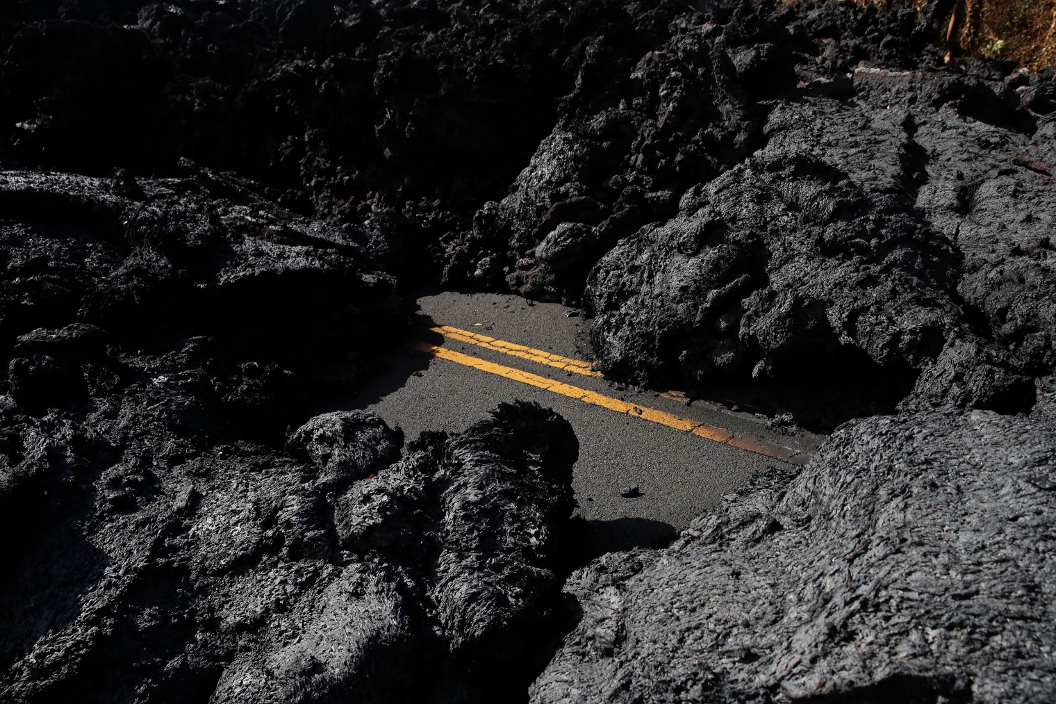 Center lane lines are partially visible along the lava-covered road in the Leilani Estates subdivision near Pahoa, Hawaii, on May 11.