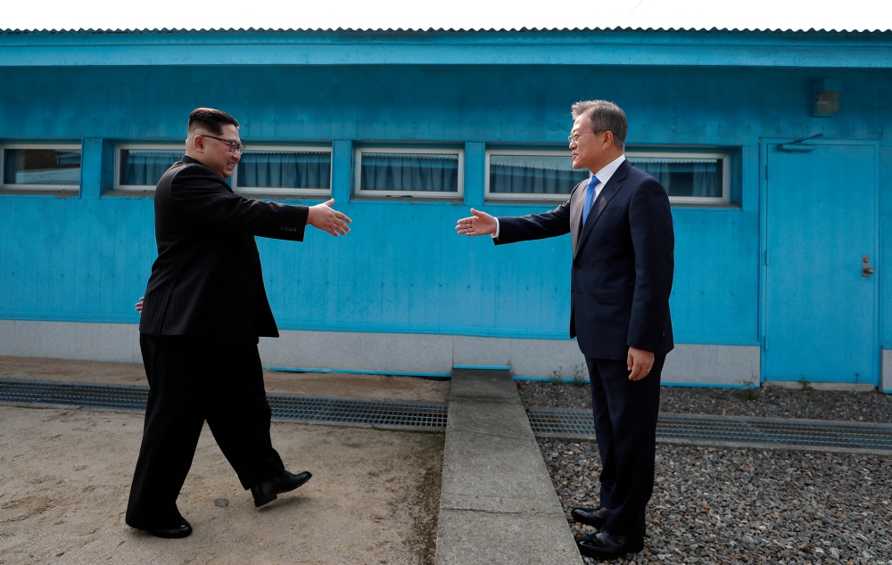 Kim, left, with Moon at the line dividing the two Koreas on April 27