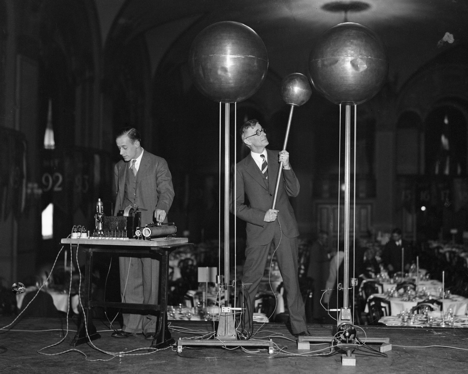 Dr. Vannevar Bush, right, and E.S. Lamar demonstrate the Dr. Robert Van De Graf 1,500,000 volt generator at the annual Dinner of Technology Alumni in the Copley Plaza. The generator is said to be capable of producing a shock of 10,000,000 volts.