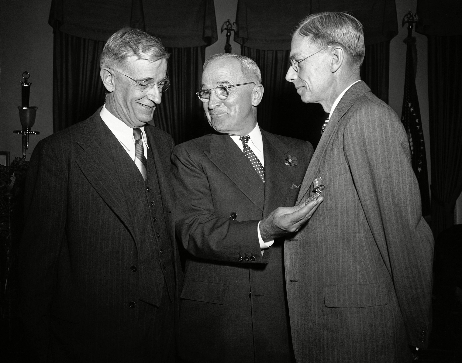 President Harry Truman, center, presents the Medal for Merit to Dr. Vannevar Bush, left, and Dr. James Bryant Conant, right, for their atomic research.