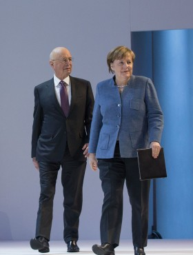 Klaus Schwab and German Chancellor Angela Merkel arrive for a plenary session at last year's WEF in Davos