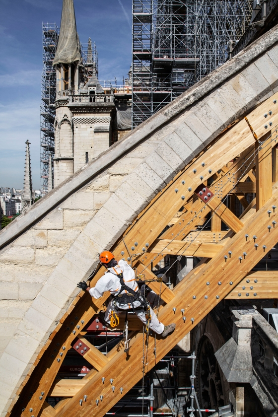 A rope-access technician installs a wooden arch to support a flying buttress on JulyÊ22, 2019.