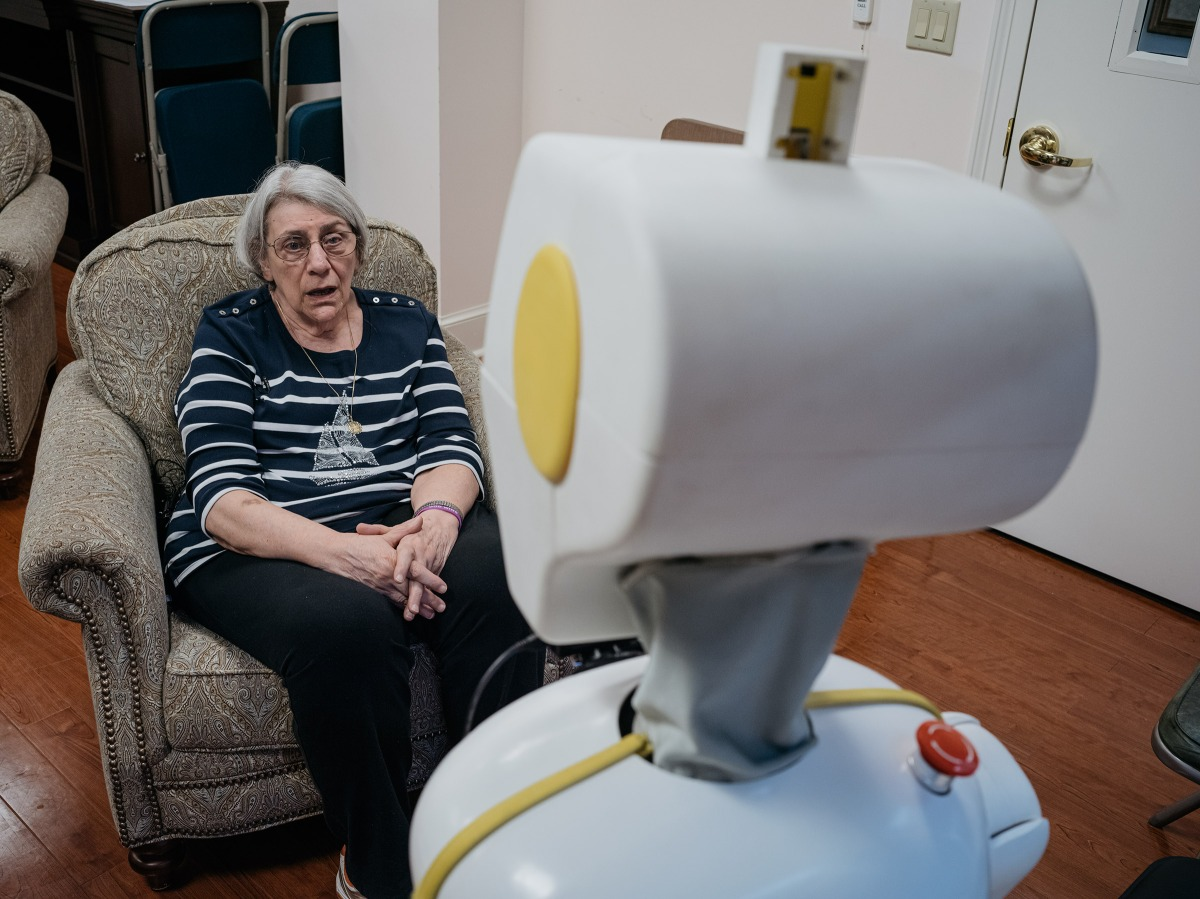 Stevie II, a robot, talks with Betty Bernard while researchers monitor the converstaion at Knollwood Military Retirement Community in Washington